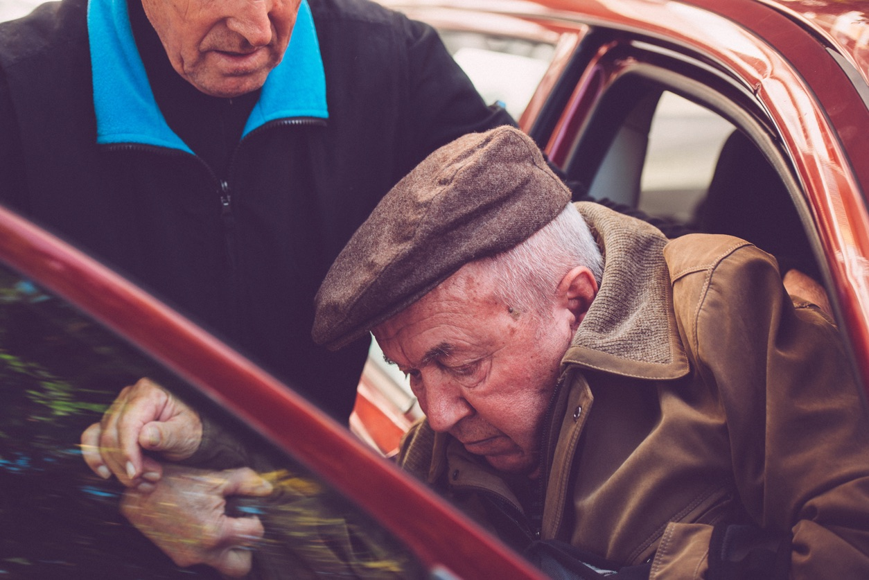 Assistent Helping Elderly Disabled Man to Leave the Car, Europe