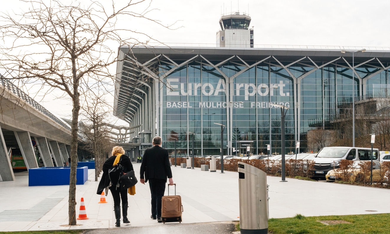 Commuters couple walking toward EuroAirport glass facade